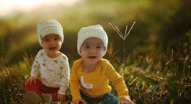 Chemo BMT transplant babies happy and sitting on grass.