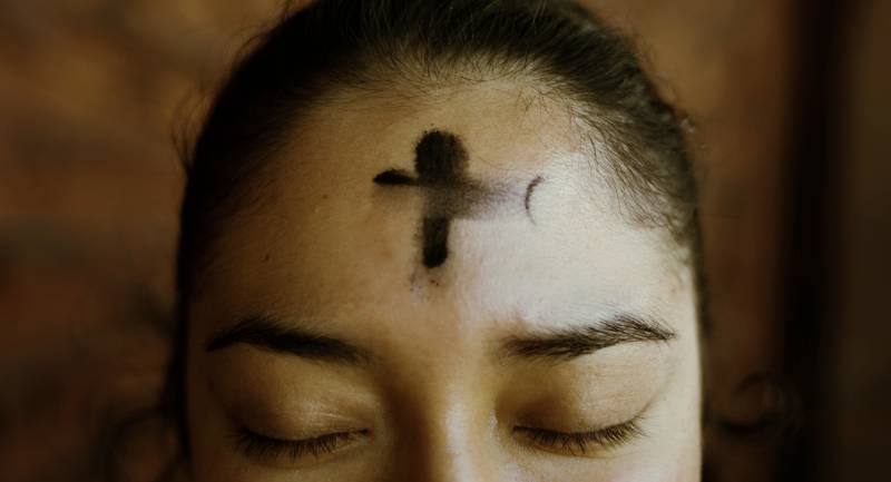 Christian cross on forehead as sign of hope and faith.