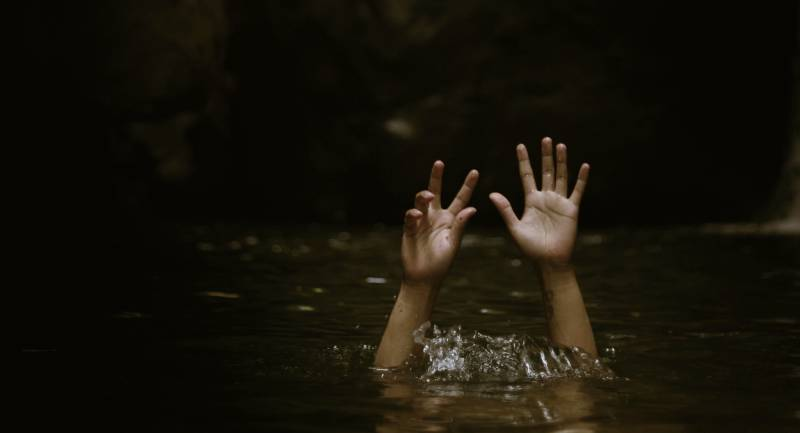 Hands reaching up from body under water as though drowning.