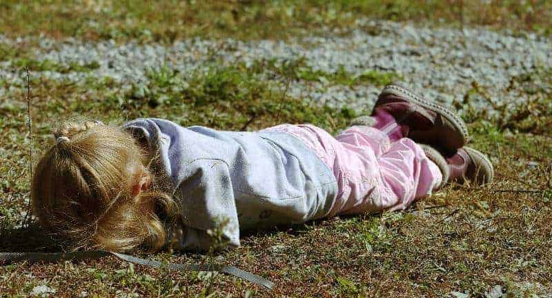 Young girl in temper tantrum laying on ground.